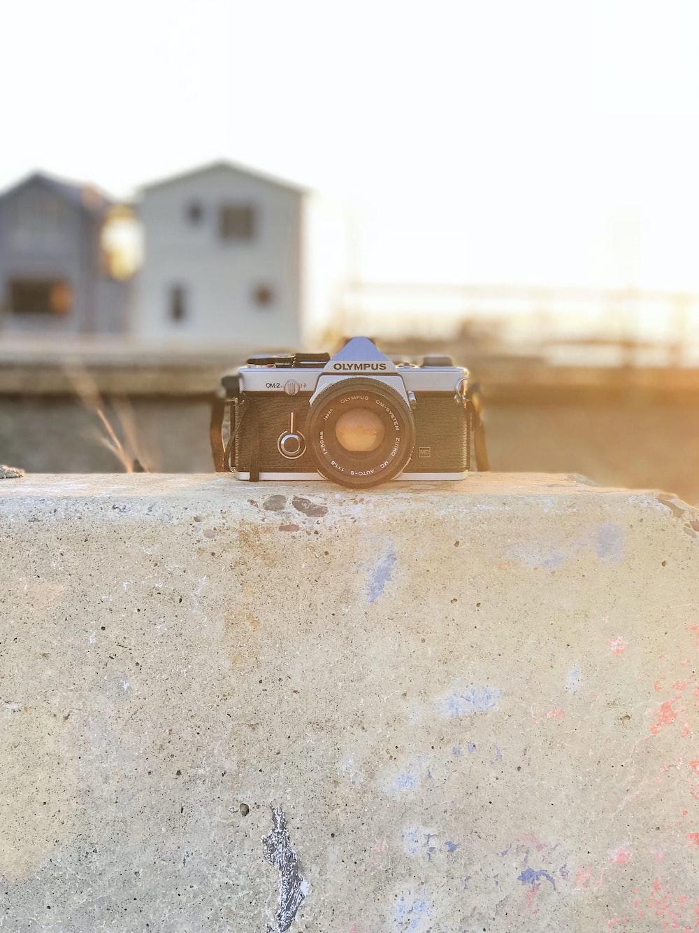 black Olympus DSLR camera on brick