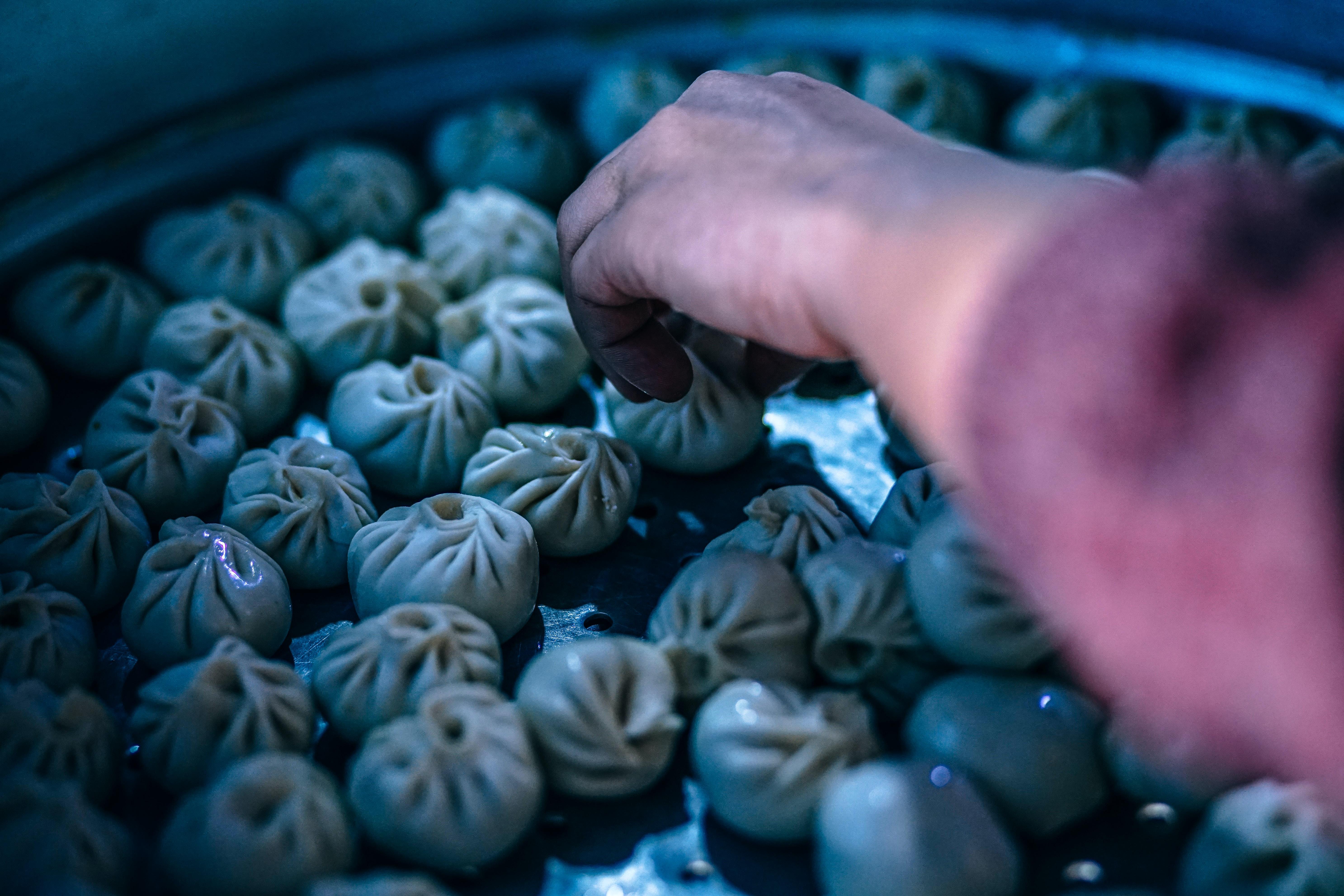 person arranging dumplings