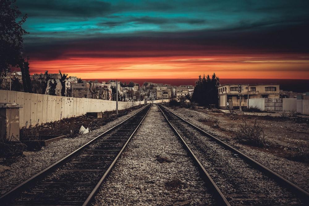 train railway near beige wall