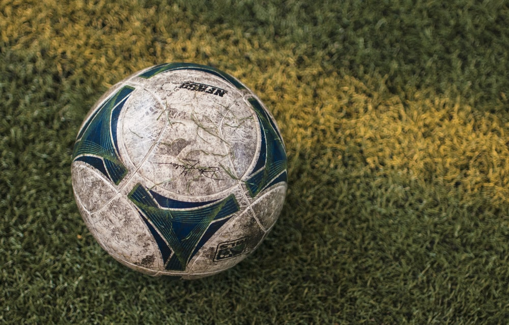 blue and white soccer ball on ground