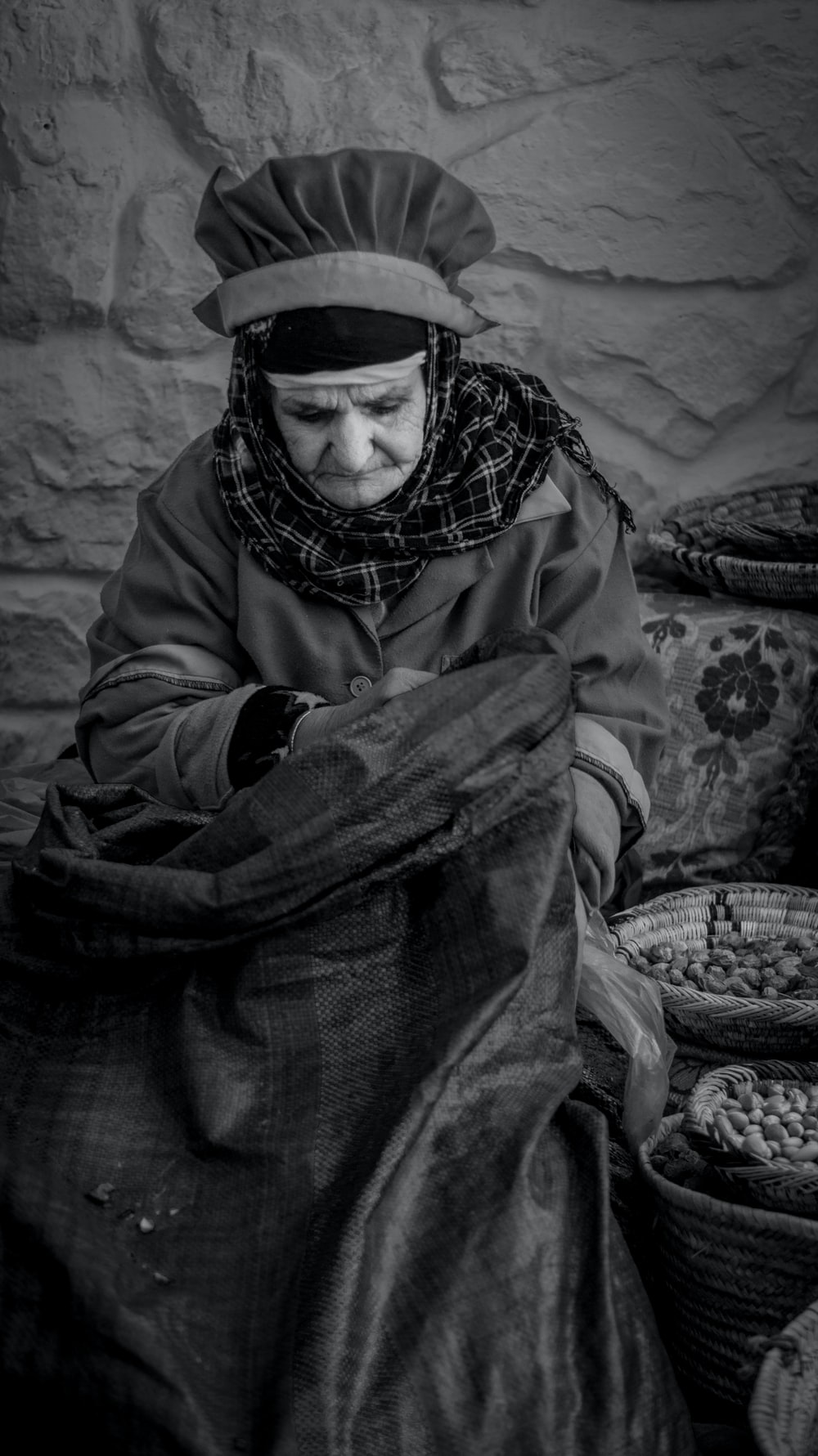 grayscale photo of woman sitting near baskets