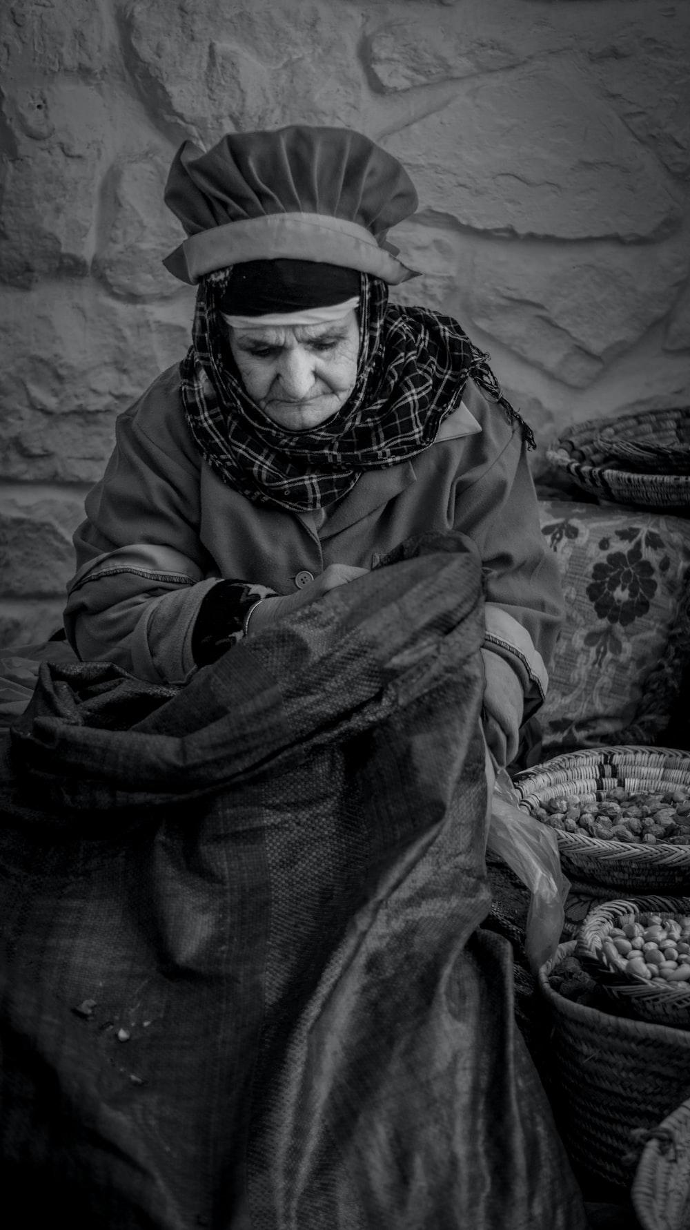 grayscale photo of woman sitting near baskets