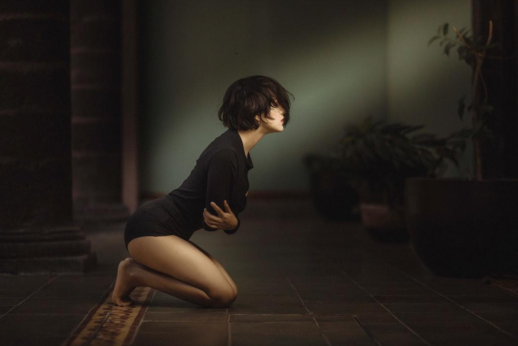 Žena klečící na zemi a držící se za lokty.