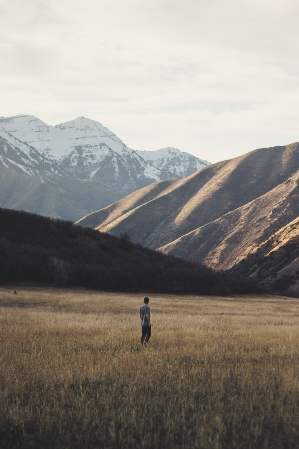 man standing on open field near mountain at daytime