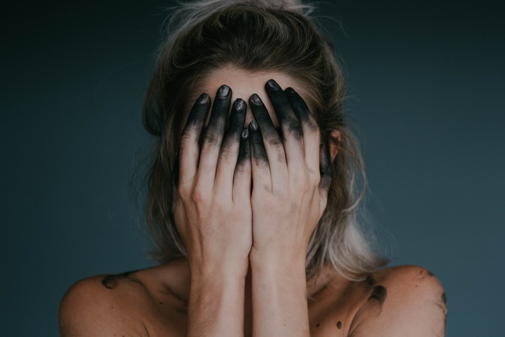 woman covering face with both hands closeup photography