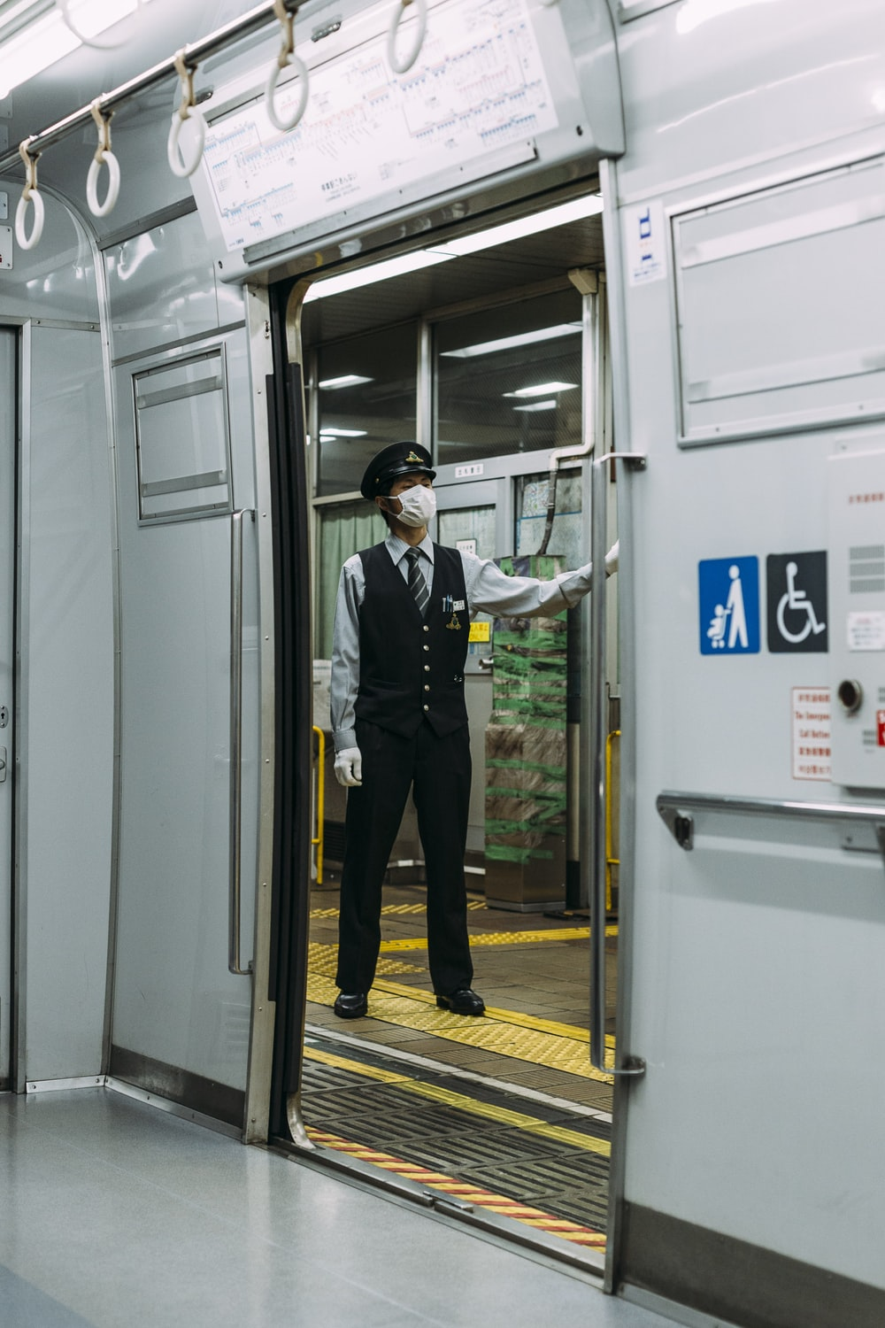 male guard in black and white dress standing infront of train station