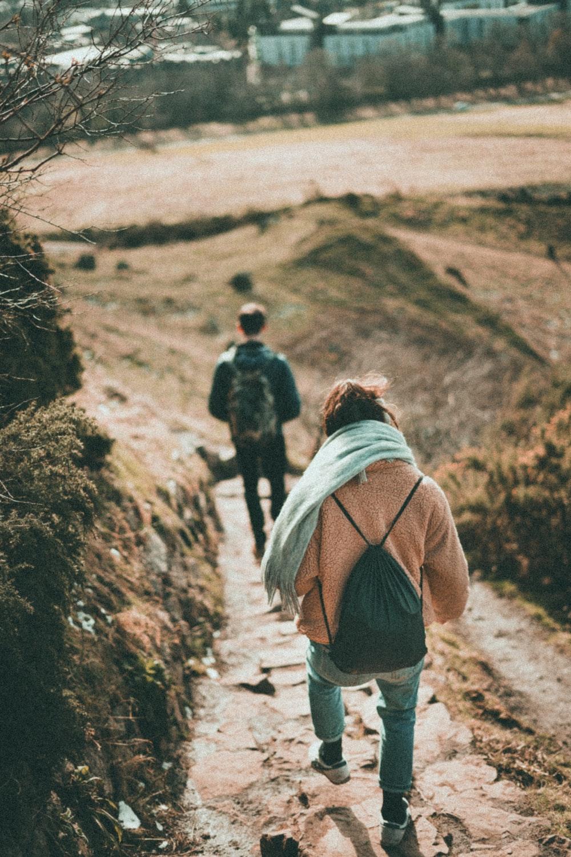 woman in blue jeans walking downhill