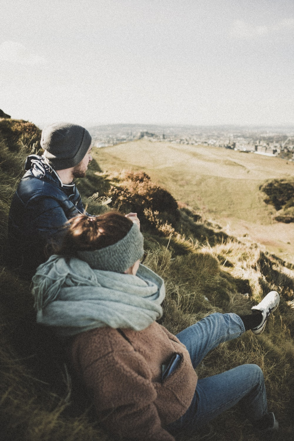 man and woman sitting on green grass while looking at city during daytime
