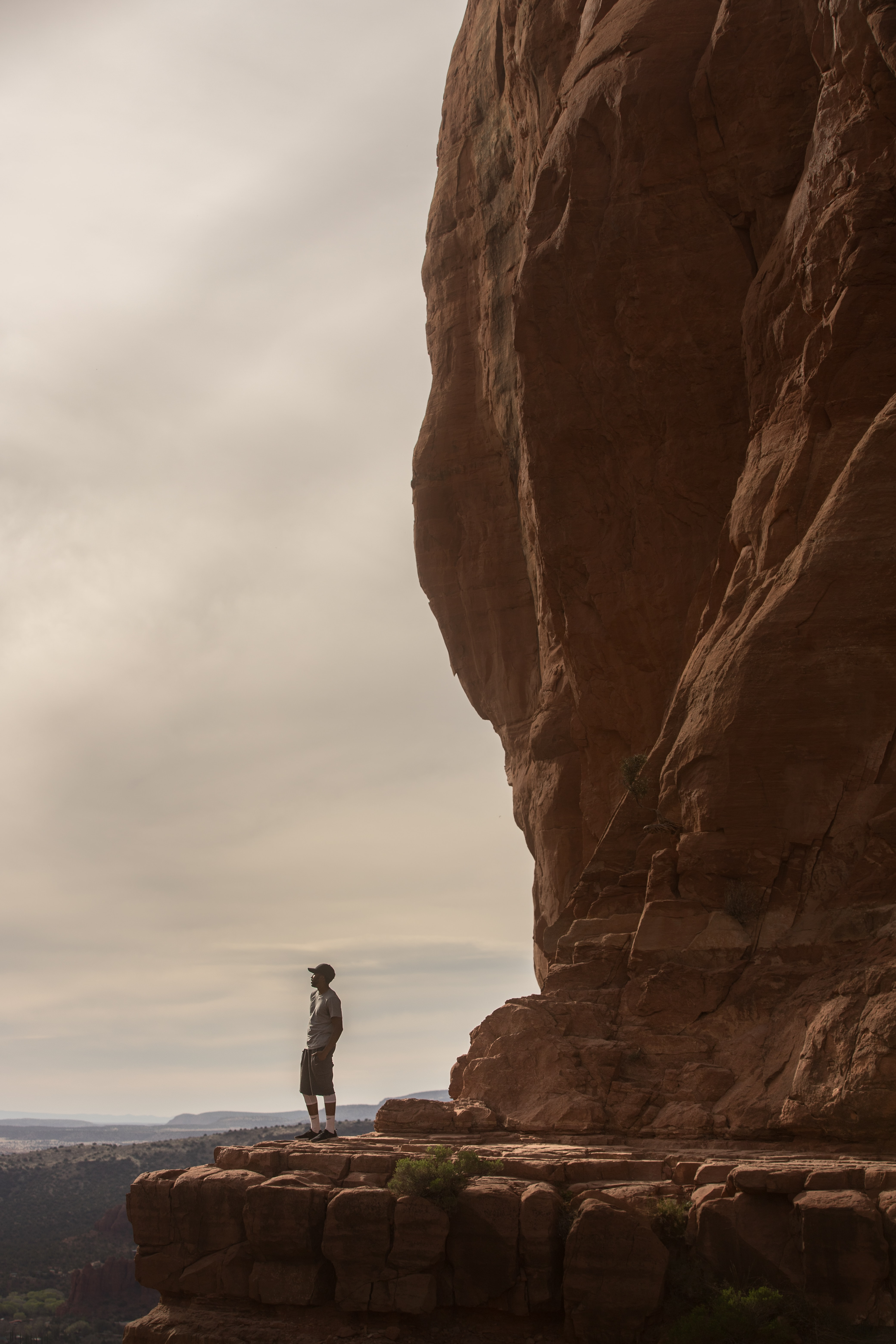 man standing at cliff of brown mountain