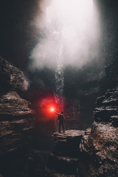 man standing on rock formation with water falls