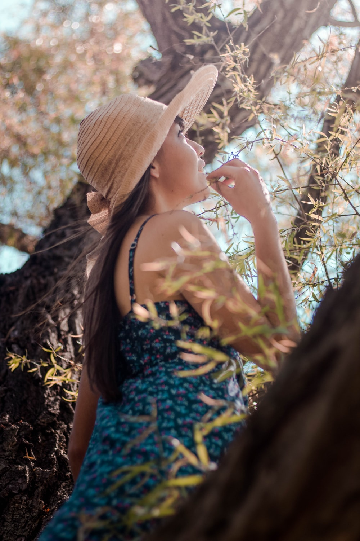 woman wearing gray sun hat beside tree