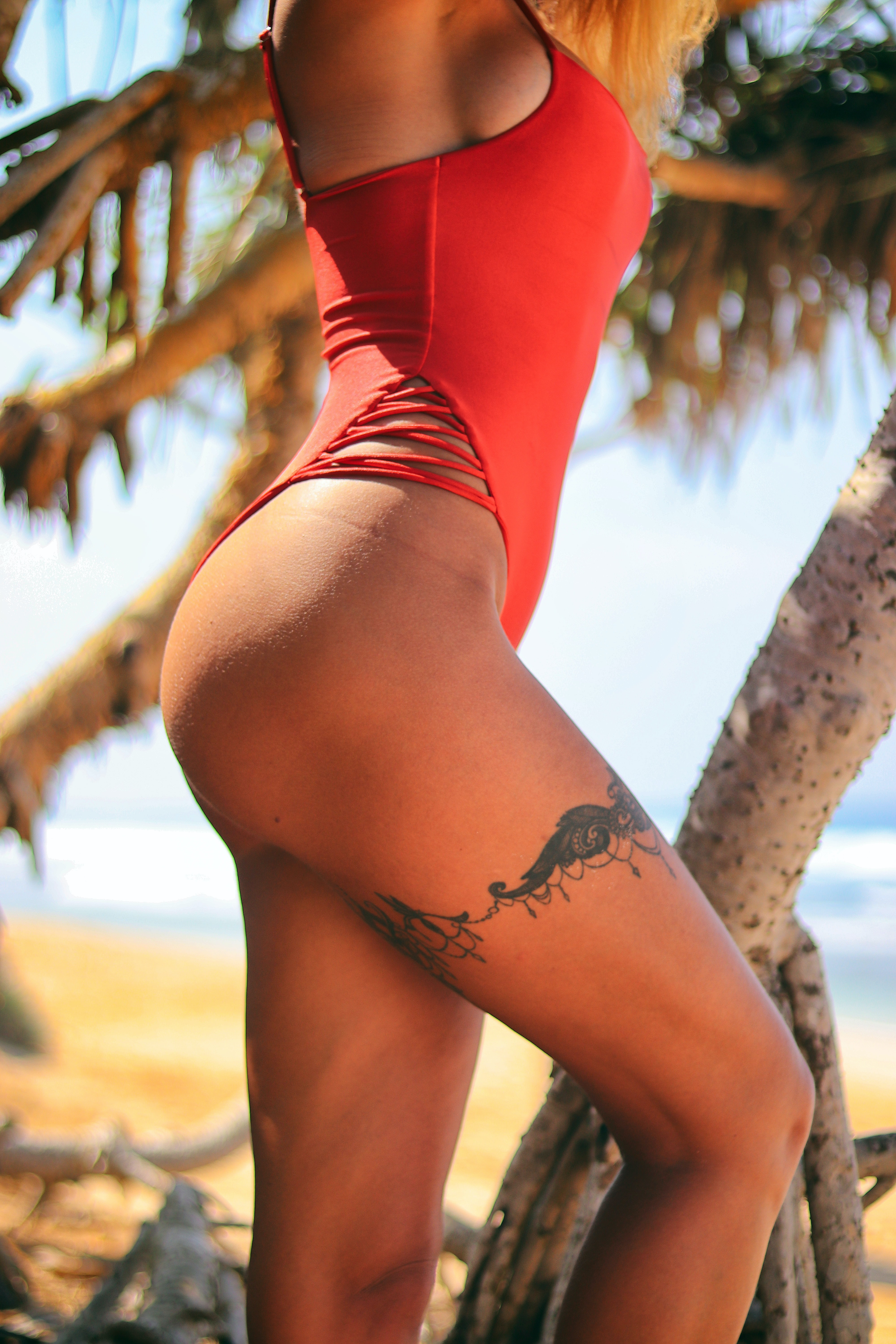 woman wearing red bikini with floral thigh tattoo