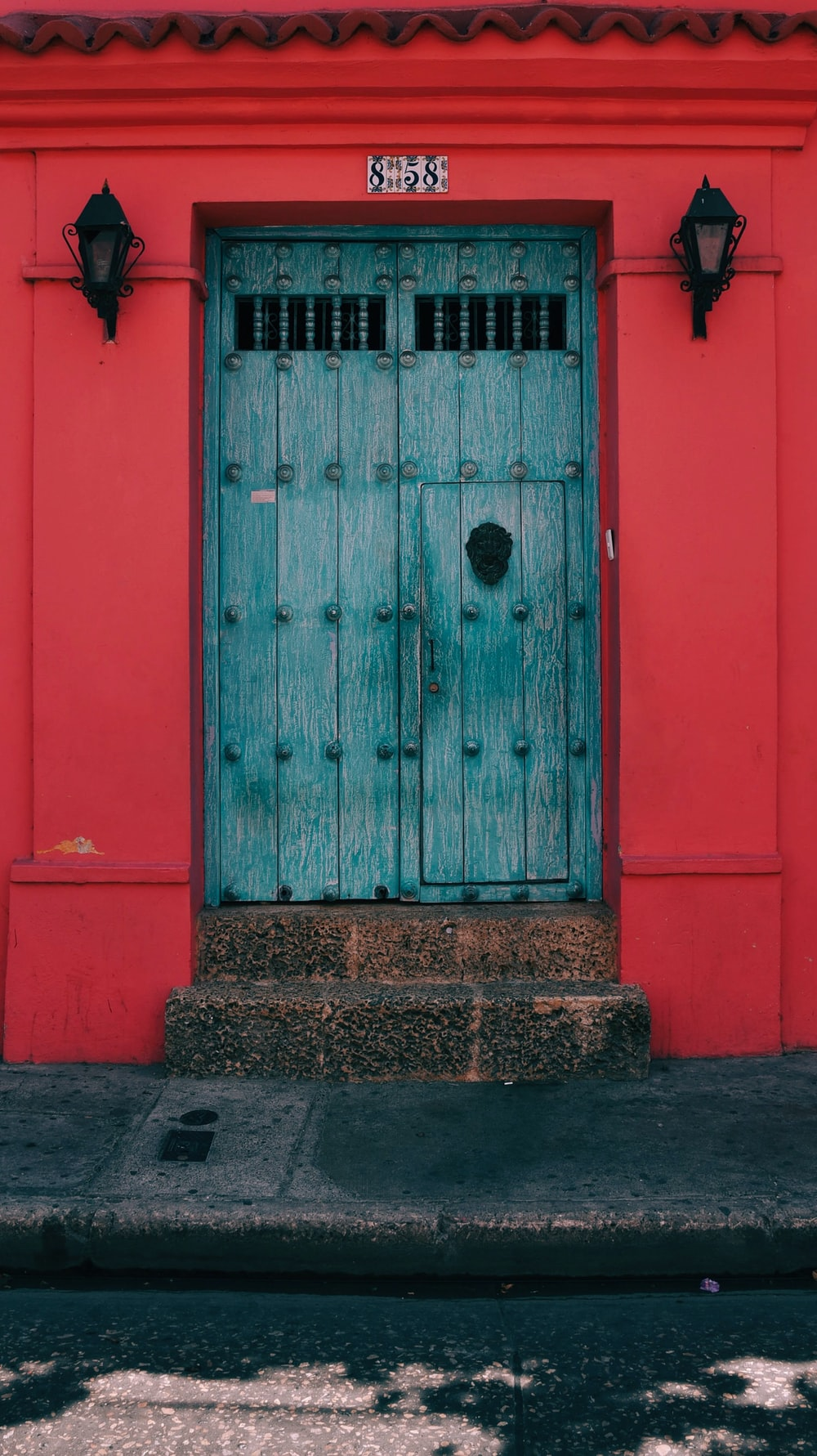 blue wooden door in red wall with light sconces