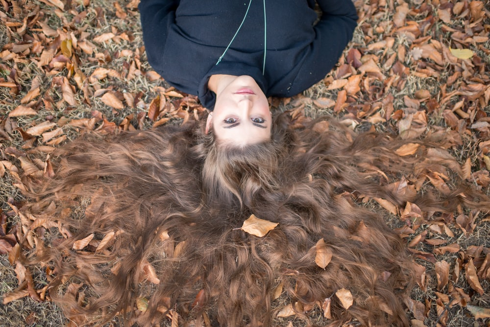 flay lay photography of brown long-haired woman wearing black crew-neck top laying on field with dry leaves