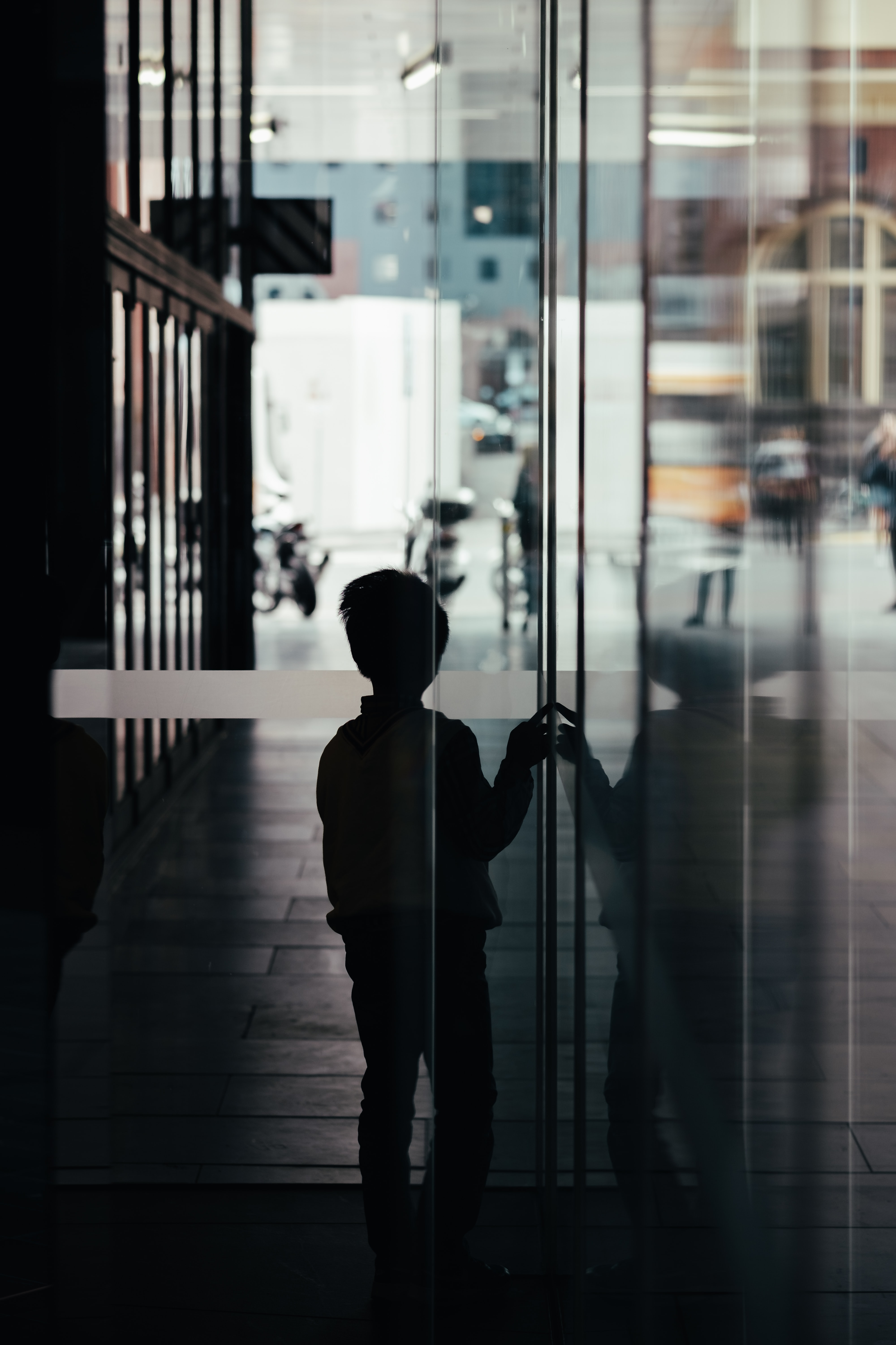 silhouette photo of boy standing near glass wall