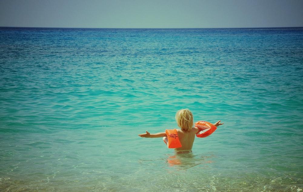 boy swimming on blue water
