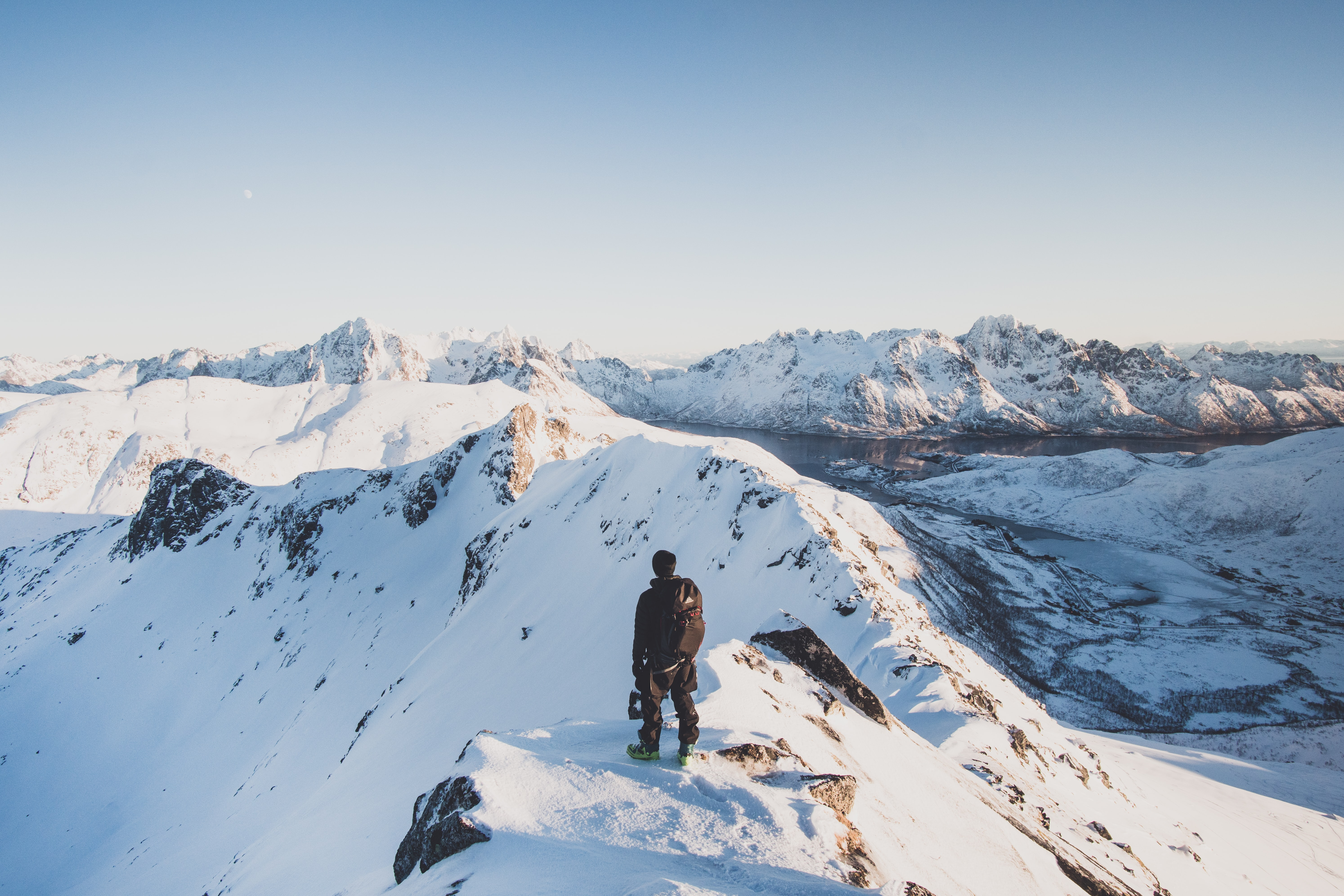 person standing on mountain overlooking sky