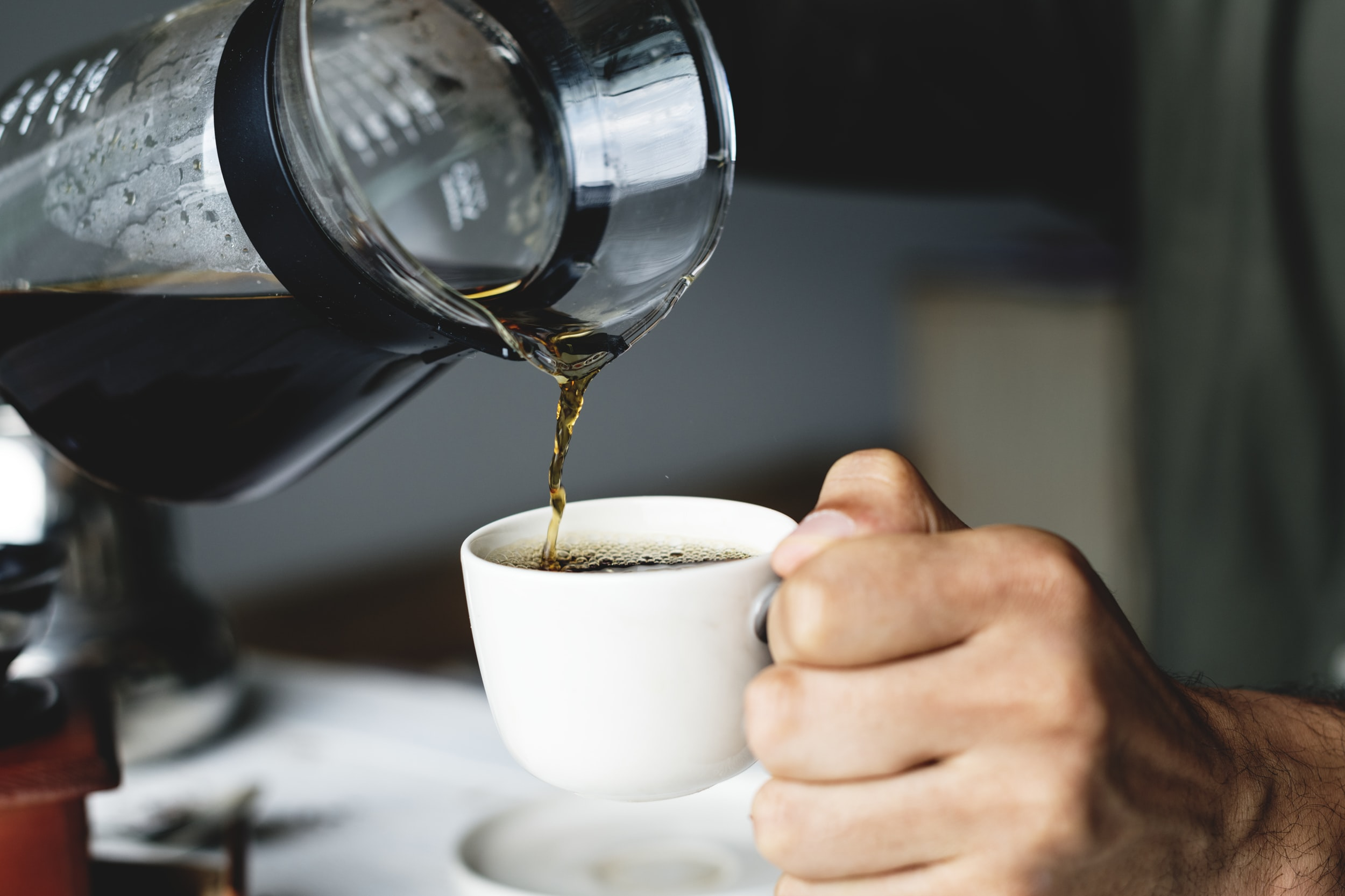 person pouring a coffee on white ceramic teacup