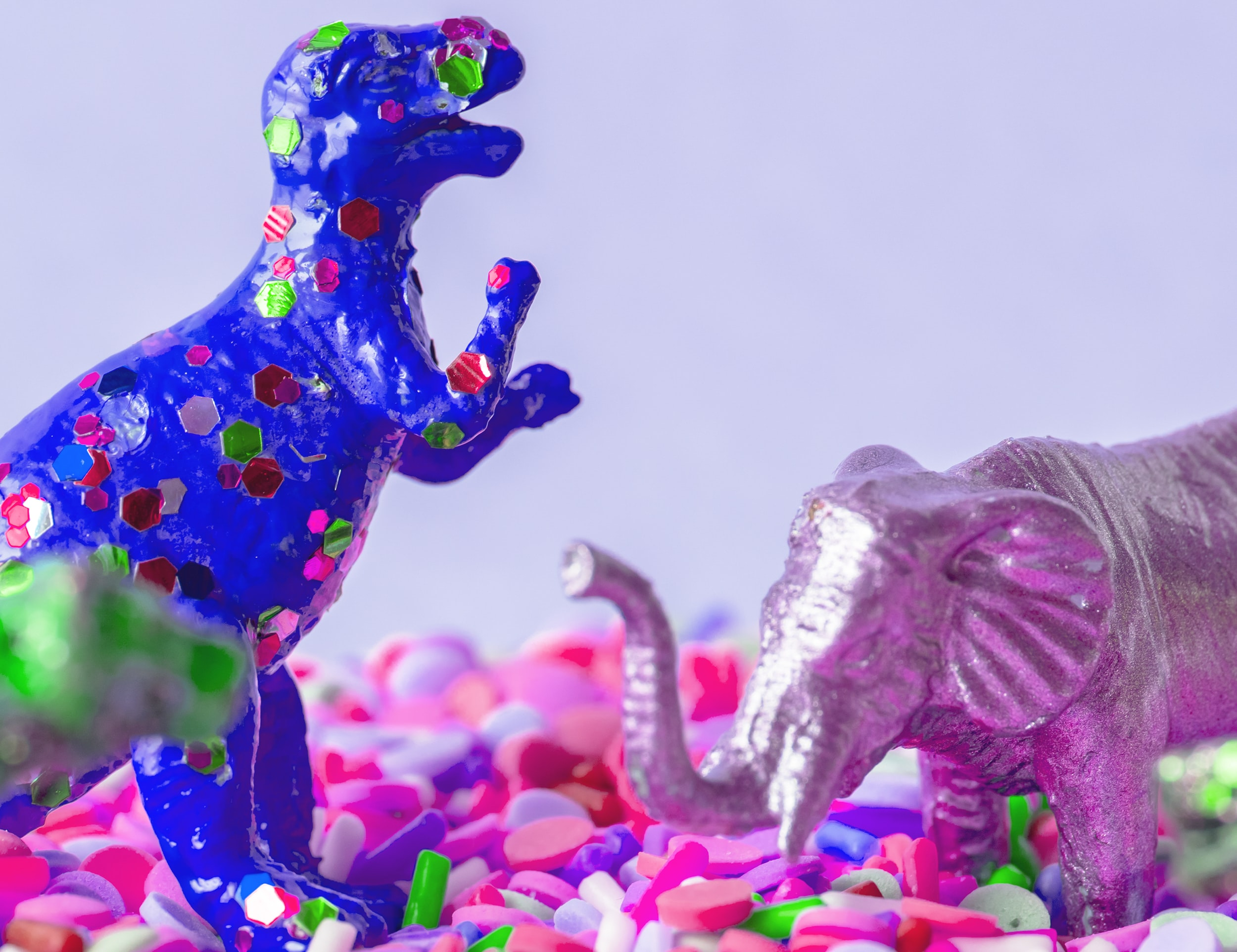 blue dinosaur and silver elephant figurines