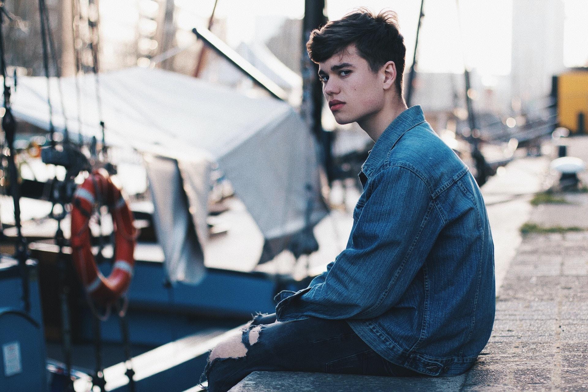 man in blue denim jacket sitting on dock