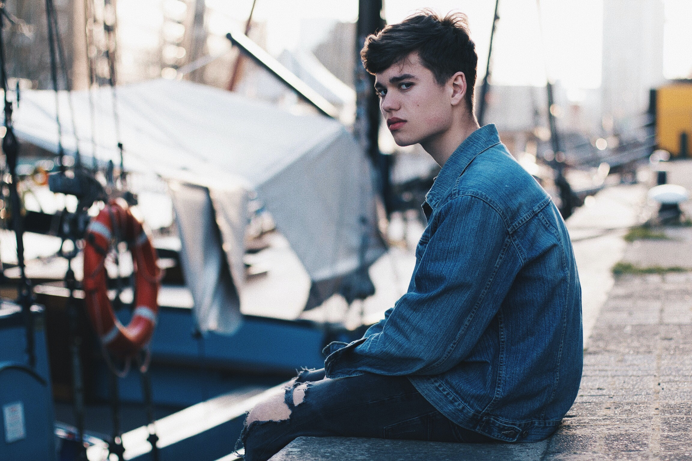 man in blue denim jacket sitting on dock
