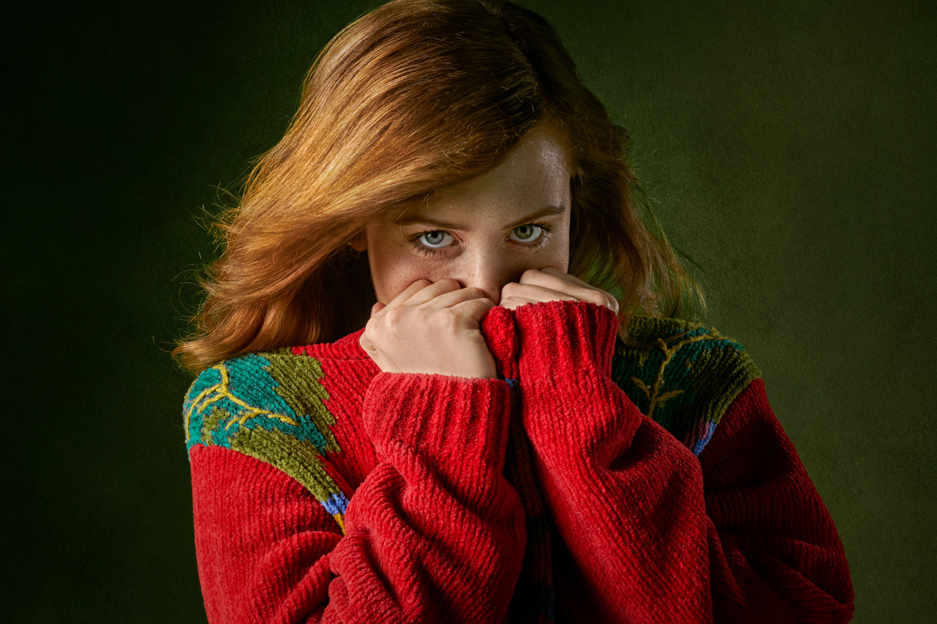 woman covering mouth with sweater