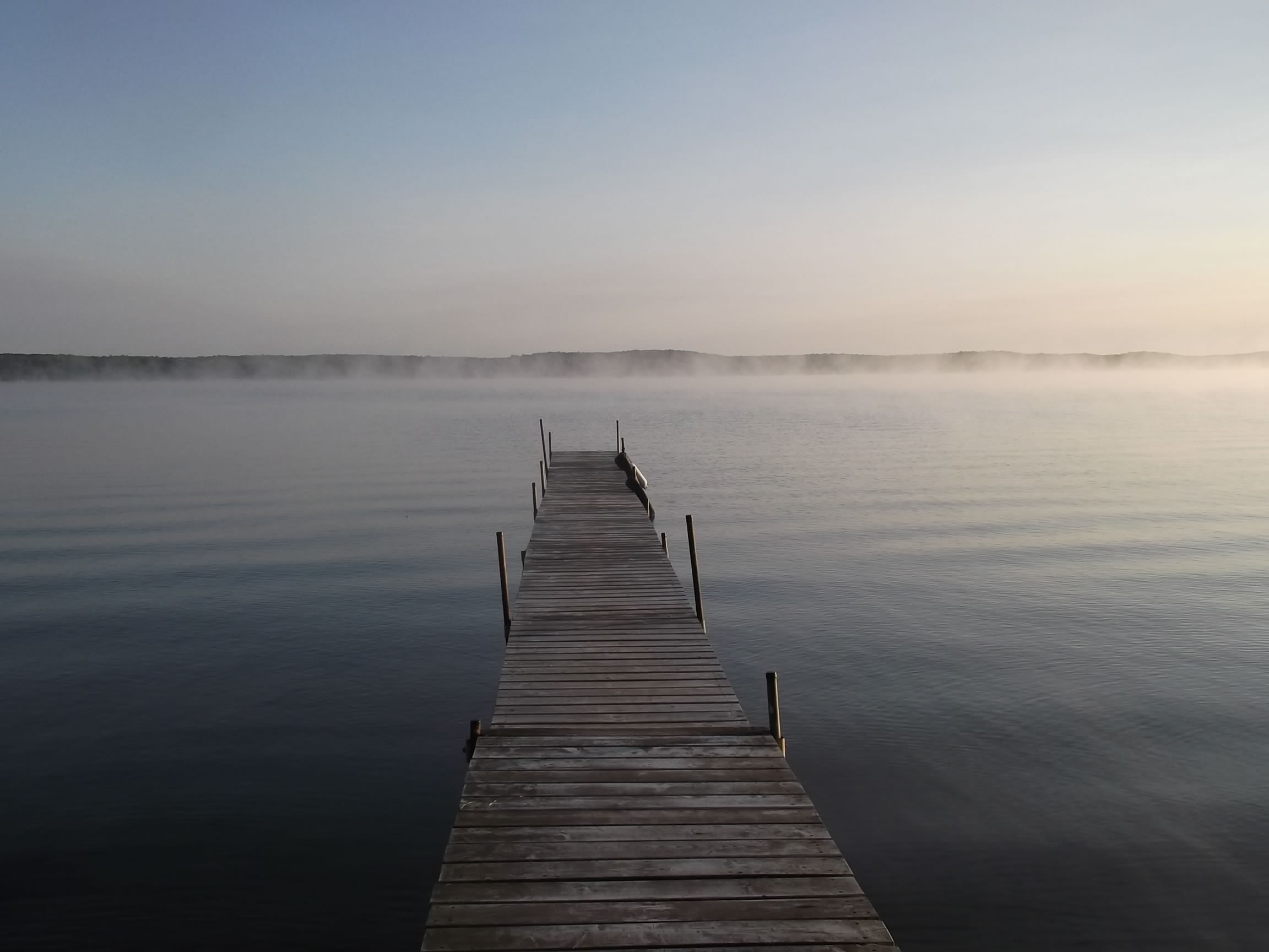 boardwalk over body of water with fogs