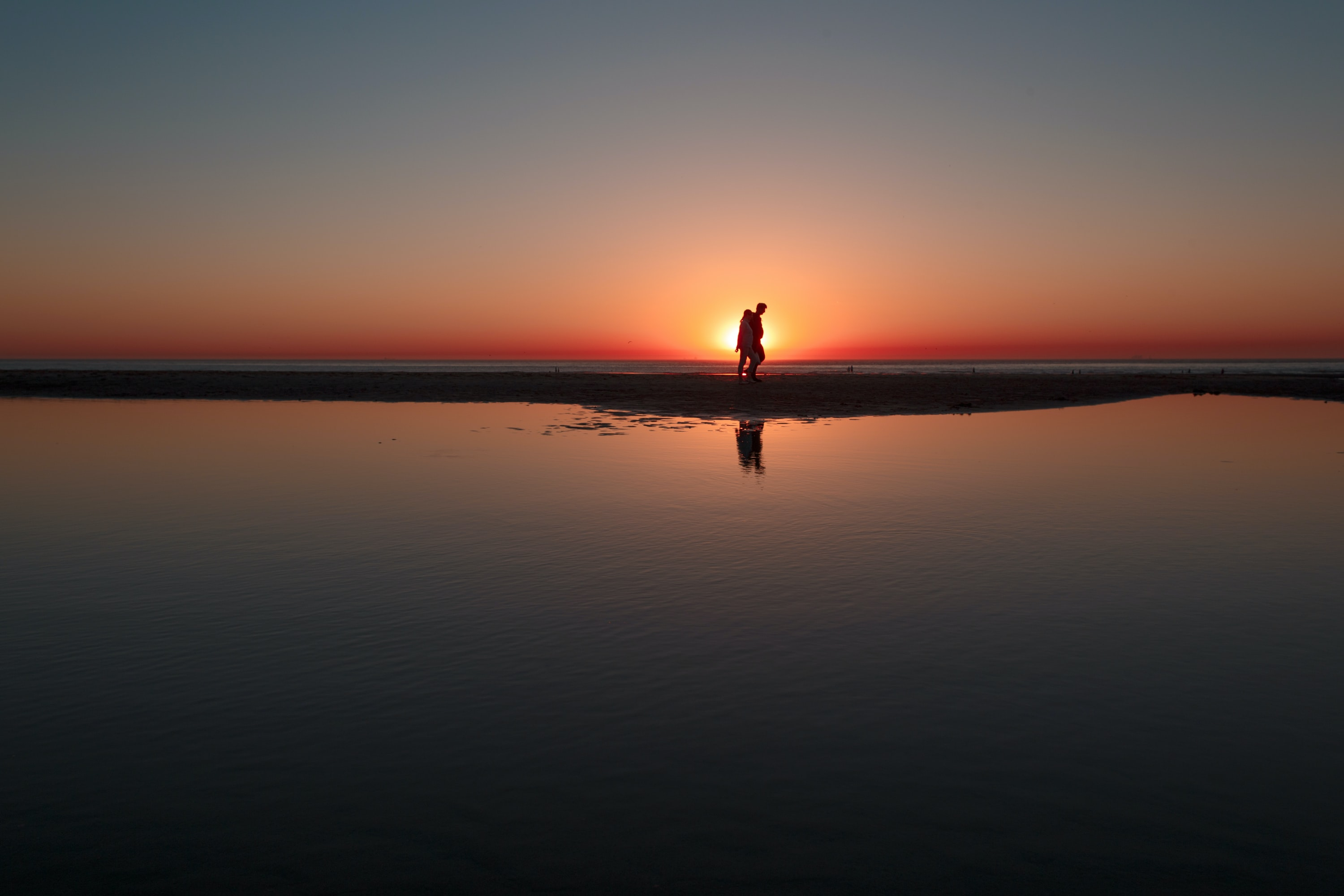 person standing across water during sunset