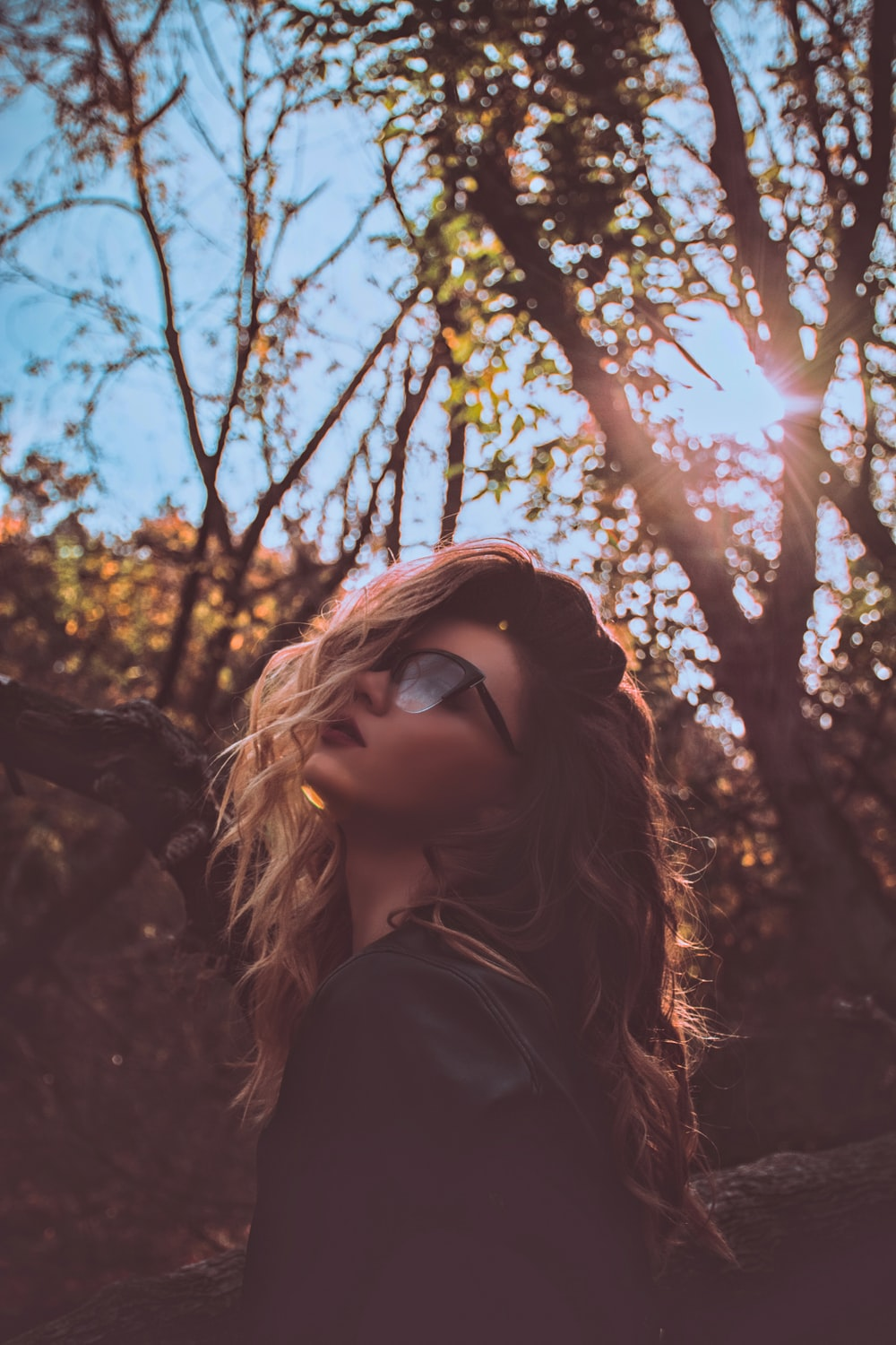 woman wearing sunglasses near trees during daytime