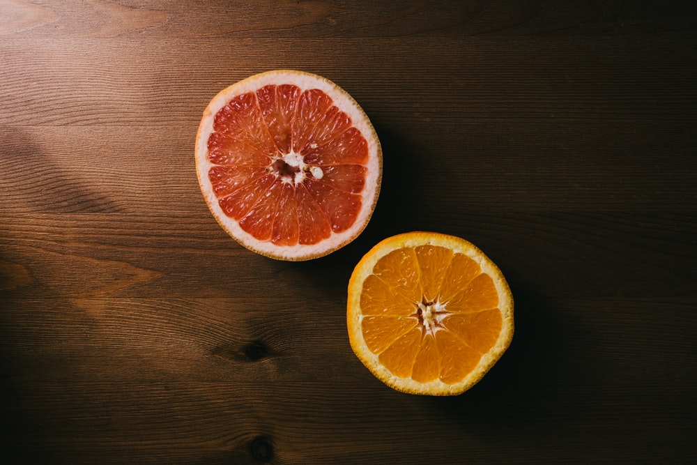 two orange and grapefruit halves on brown wooden surface