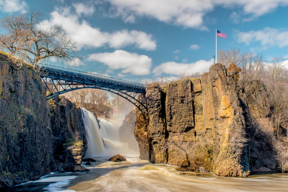 bridge over river near waterfall