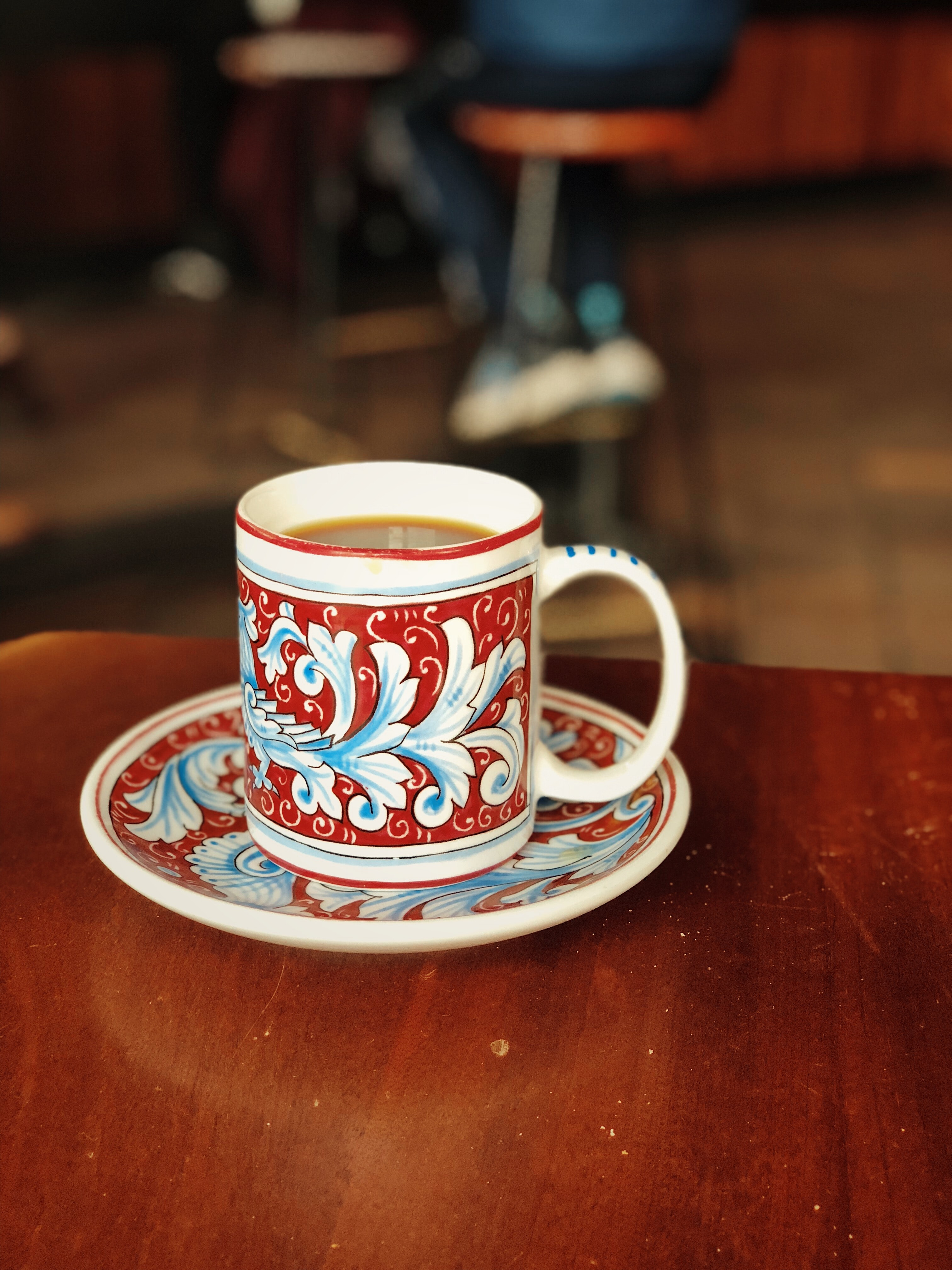 white and red ceramic mug on saucer with brown liquid