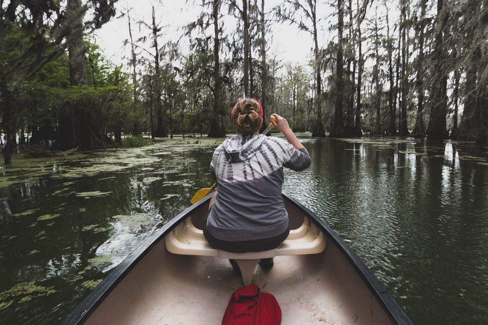 woman rowing boat on lake