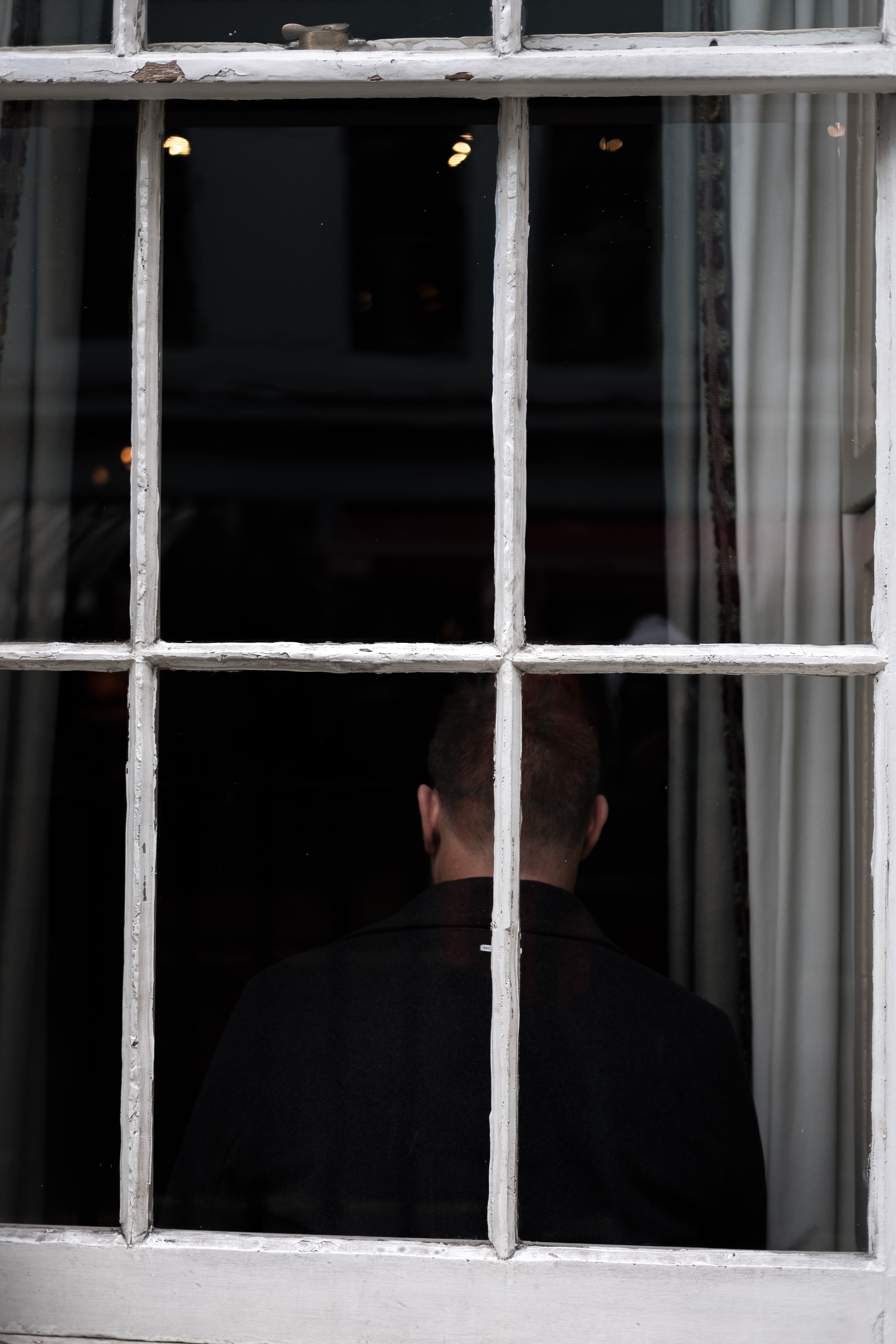 man standing front of glass window