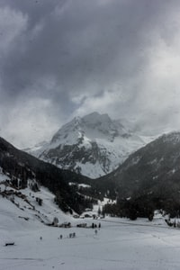 grayscale of alpine mountain covered by dark clouds