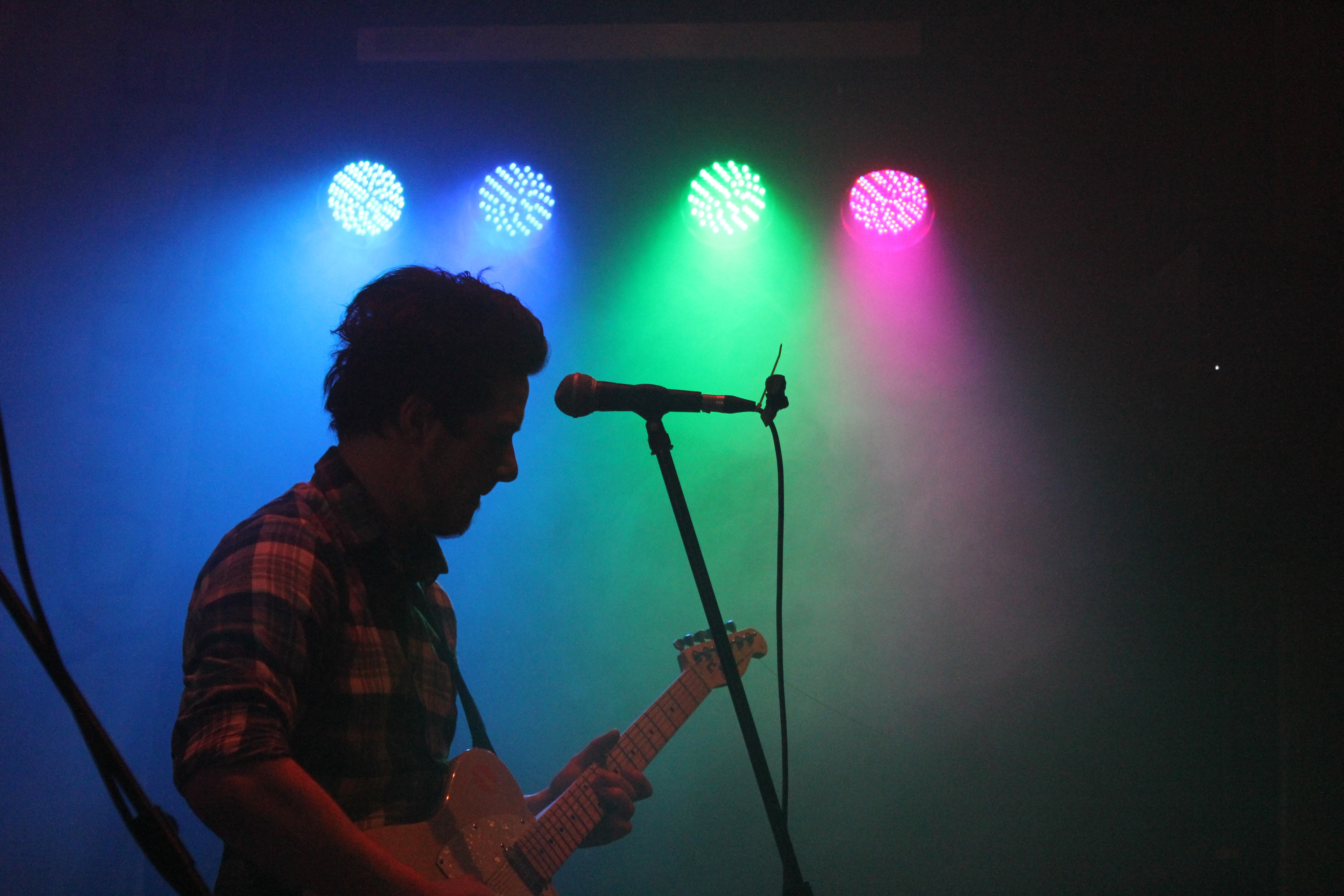 man playing guitar with stage lights