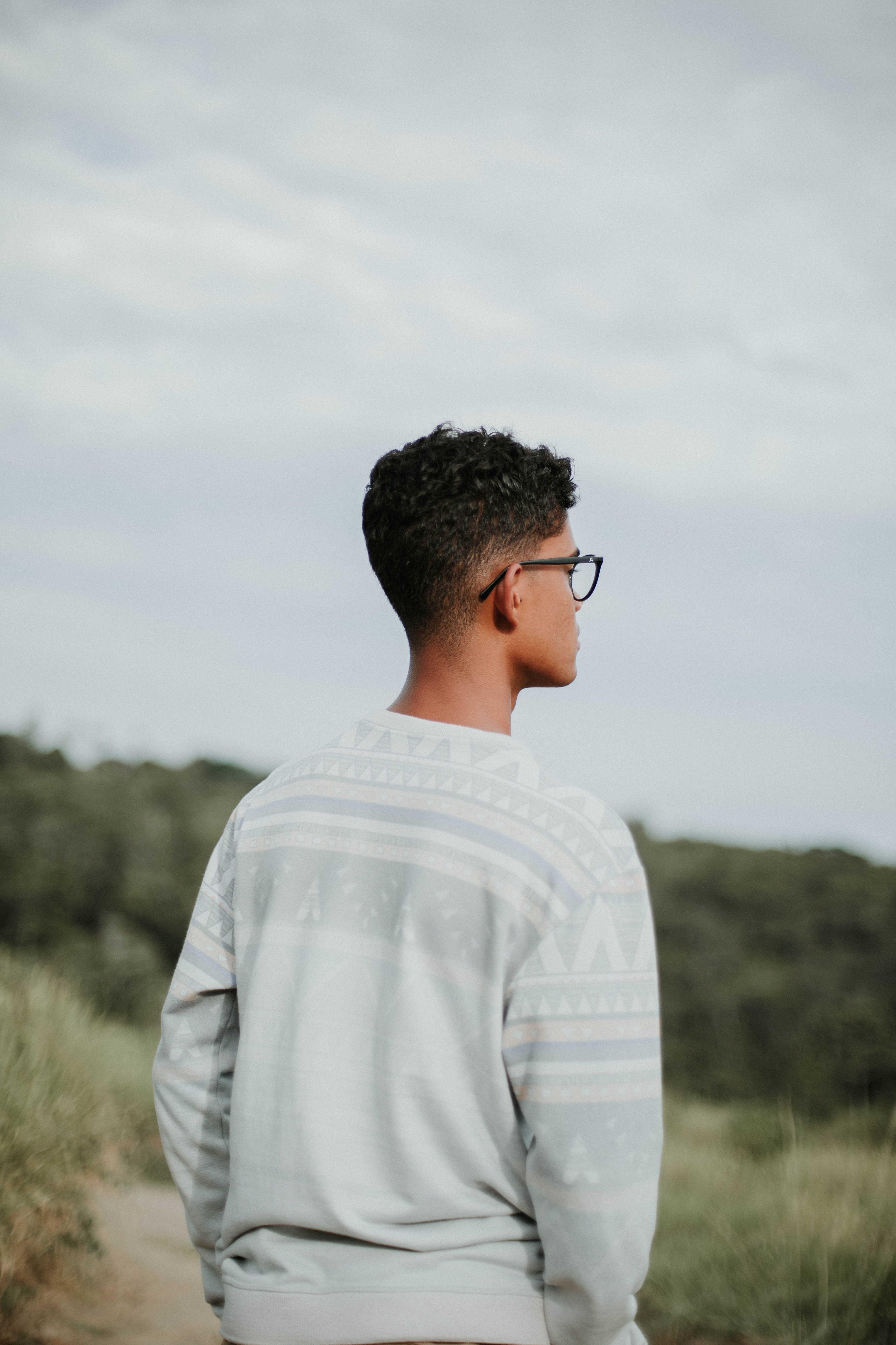 man wearing sweater facing forest