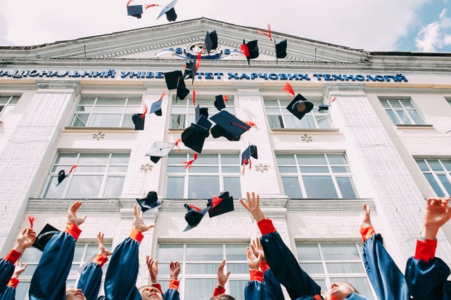 group of fresh graduates students throwing their academic hat in the air