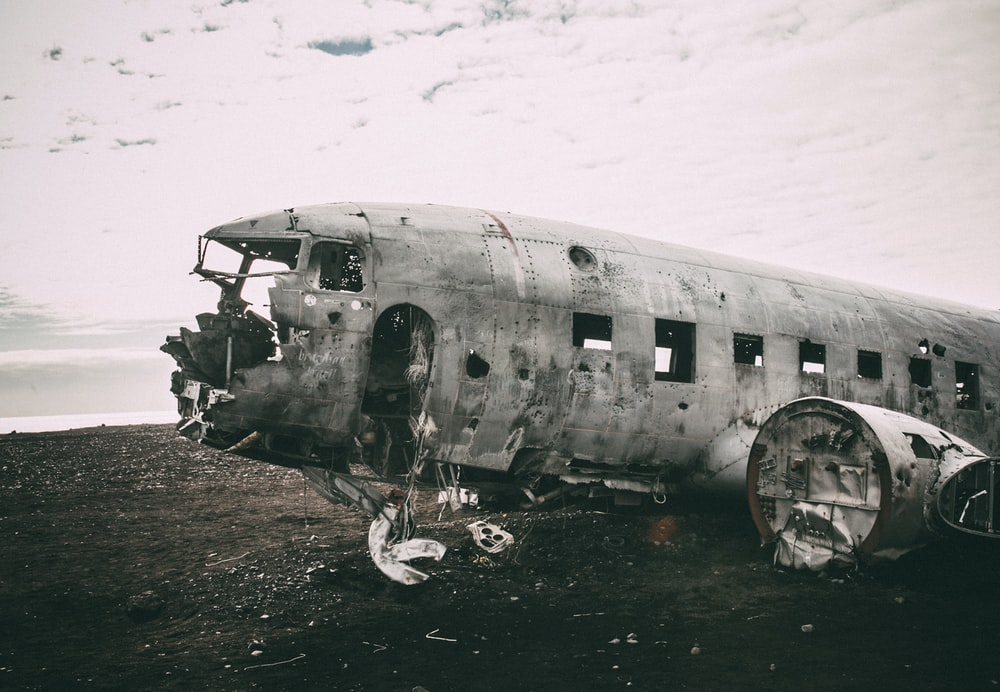 grayscale photo of abandoned airliner in open field