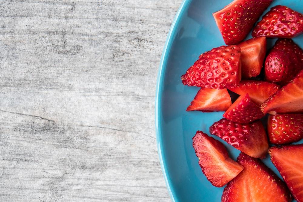 sliced strawberries on teal ceramic plate
