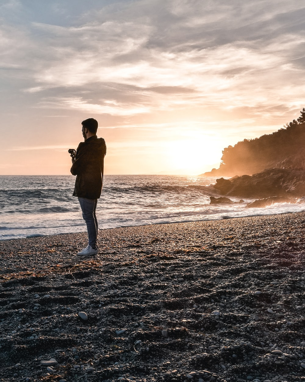 man wearing jacket standing on beach during golden hour