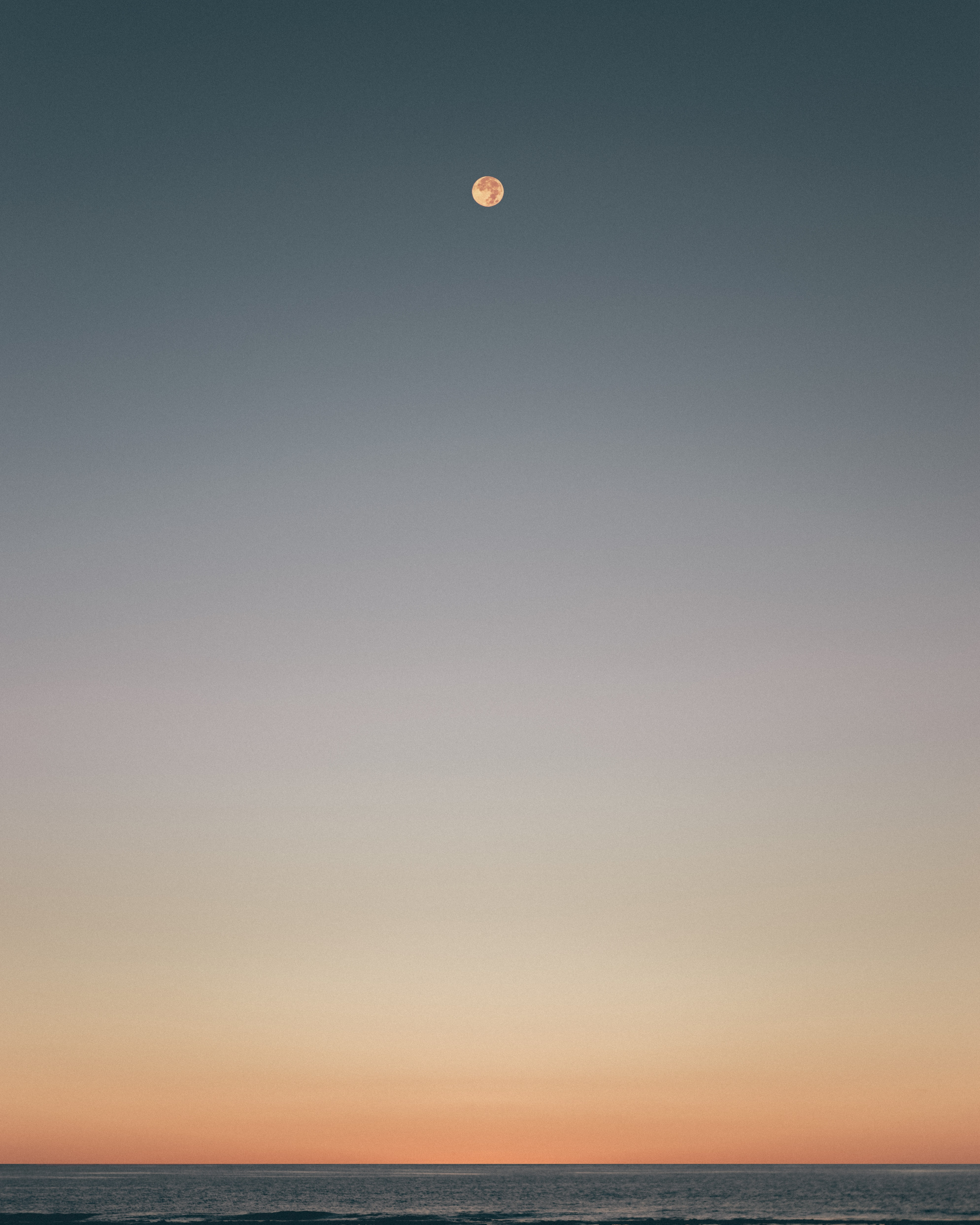 moon over body of water during sunset