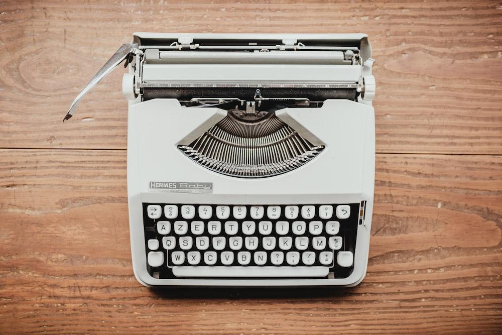 white and black typewriter on table