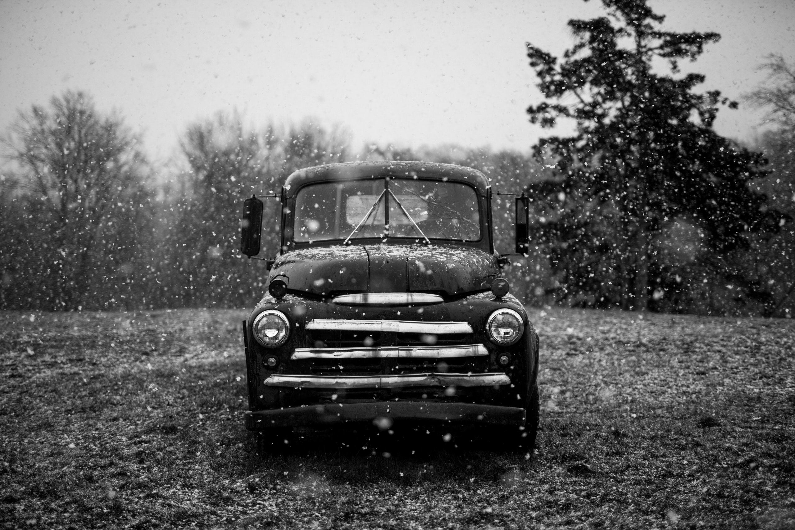 grayscale timelapse photography of classic vehicle on rainy season