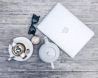 silver MacBook beside white ceramic teapot