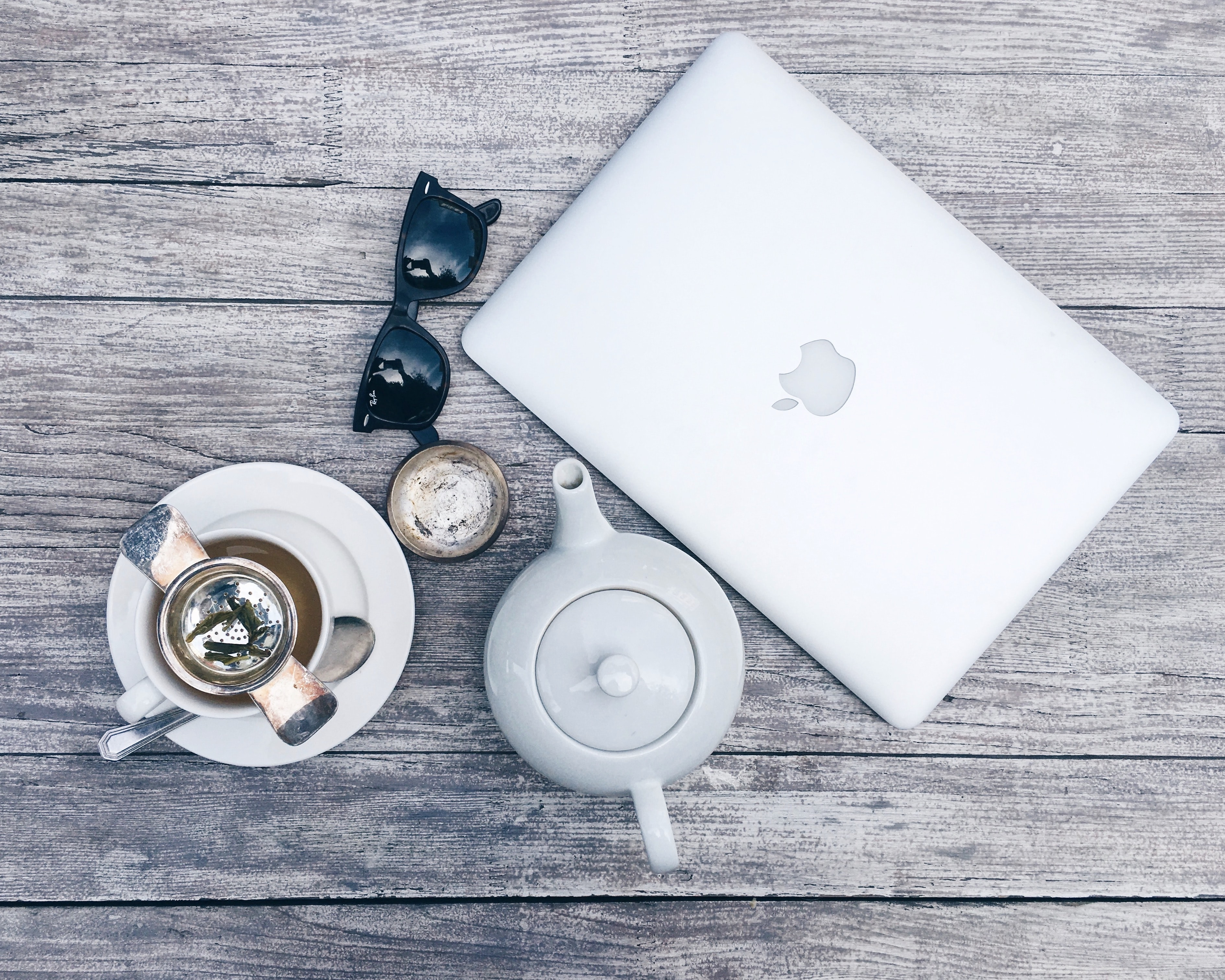 silver MacBook beside white ceramic teapot