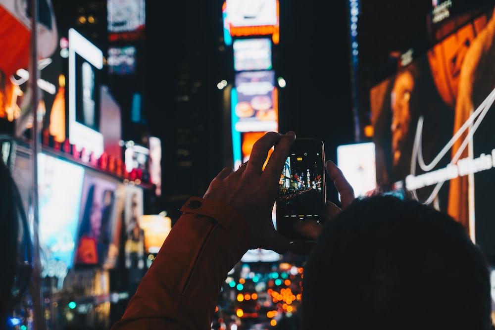 man taking photo of street using smartphone
