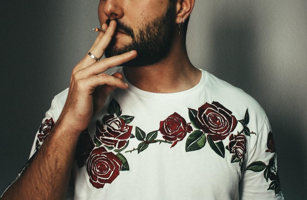 man smoking cigarette near wall