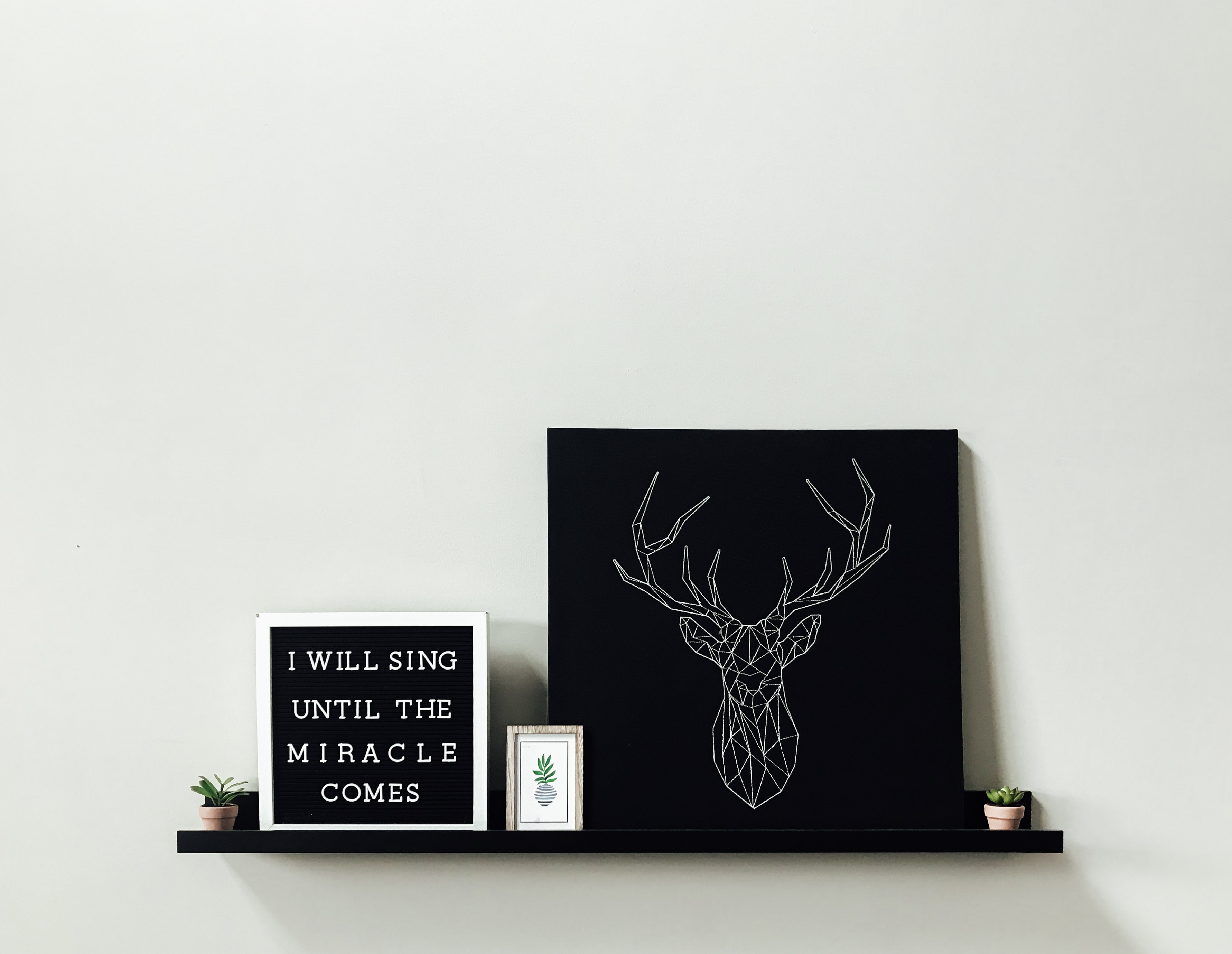 white reindeer wall decor on black floating shelf