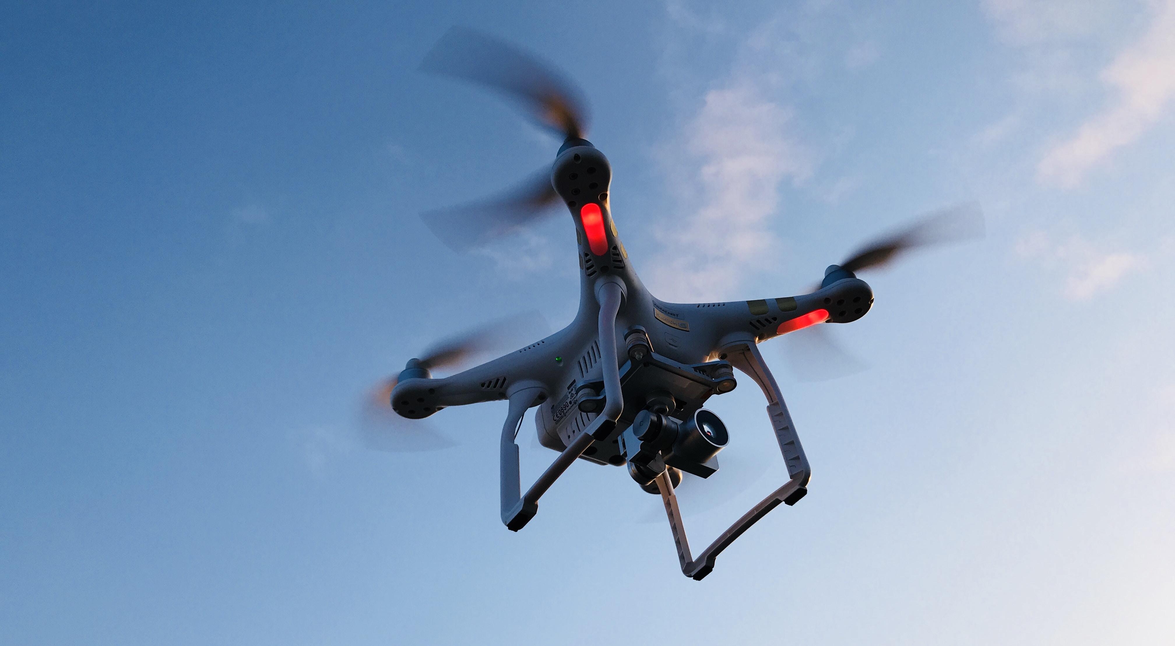 drone flying under white sky